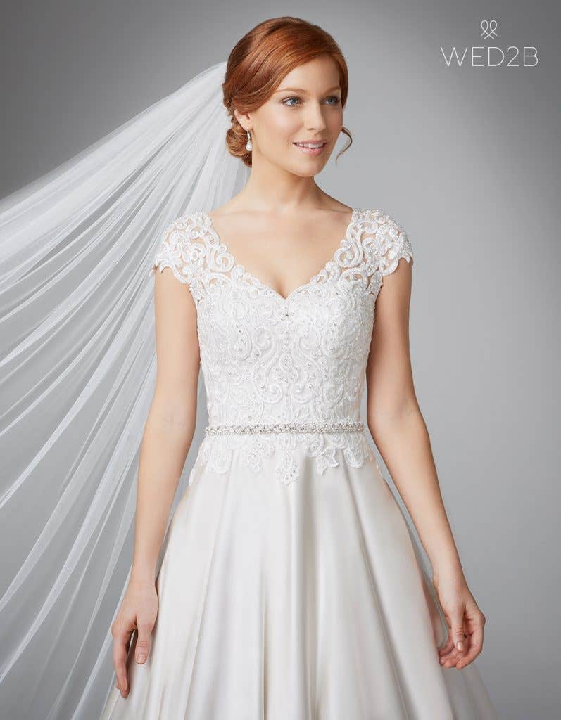 Close-up front view of Dawson in oyster, a princess wedding dress, with bridal belt Estella