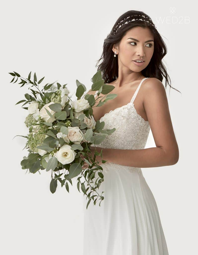 front crop view of Lark with a bouquet a boho wedding dress