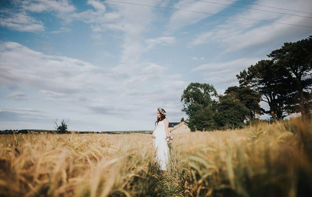 Victoria in a field holding her baby bump at her outdoor wedding