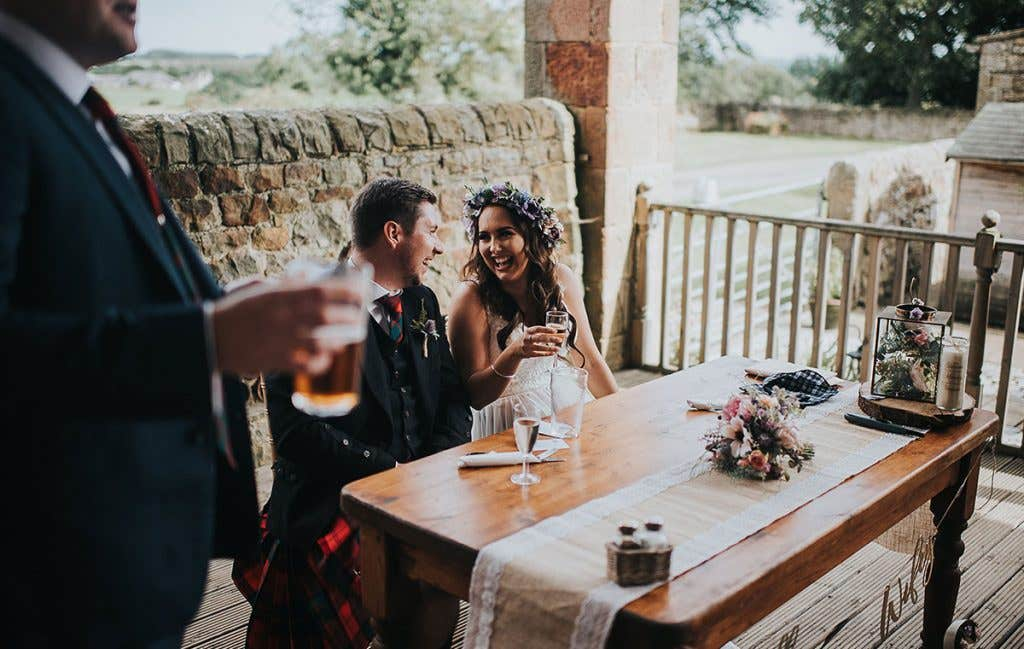 Victoria and Stuart at their head table at their outdoor wedding