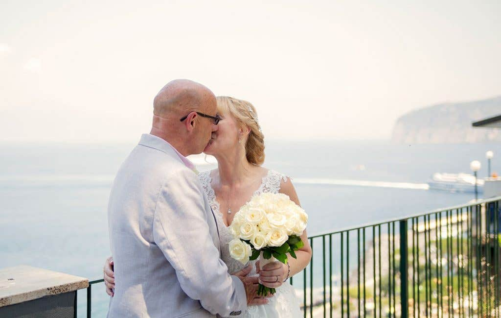 Elizabeth and Mark kissing overlooking the sea at their destination wedding
