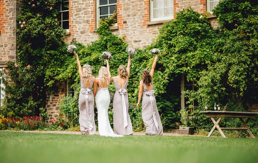 Charlotte with her bridesmaids holding up their bouquets on her rustic wedding day