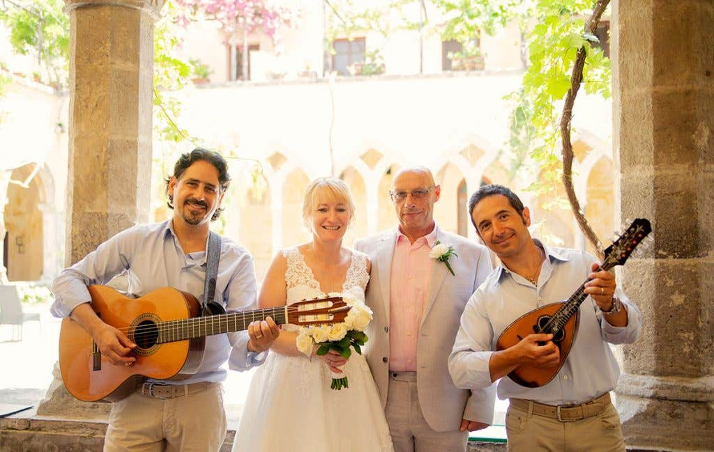 Elizabeth and Mark with the guitar and mandolin players at their destination wedding