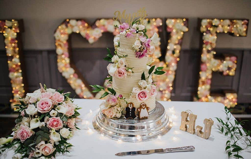 A beautiful floral decorated 4-tier wedding cake at this Hertfordshire wedding
